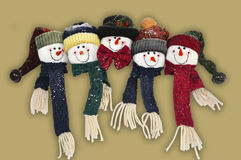 Snowman family with happy faces. Snowman family happy faces on gold background with smooth shadows stock photography