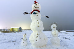 Snowman family on the meadow at night Royalty Free Stock Photo