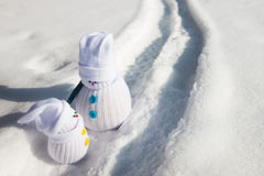 Snowman-father and snowman-kid having conversation. Two hand-made toy snowmen on a snowy path Stock Image