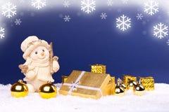 Snowman figure and golden ornaments. Golden xmas ornaments and snowman figure on snow Royalty Free Stock Photo