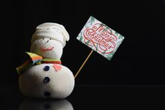 """Snowman, paperboard sign on a stick, text """"Merry Christmas!"""". Snowman figure holding a paperboard sign on a stick with text """"Merry Christmas stock images"""