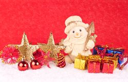 Snowman figure on red background. Cute snowman figure with stars , xmas balls and stars in snow Stock Images