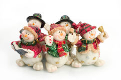 Snowman figures. Miniature Snowman statues in different poses against white background with clipping paths royalty free stock image