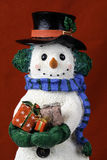 Snowman Figurinne. Snowman figurine with top hat and scarf holding several wrapped presents on red background Royalty Free Stock Photography