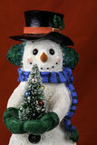 Snowman Figurinne. Snowman figurine with top hat and scarf holding small decorated Christmas tree on red background Royalty Free Stock Image