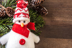 Snowman and fir branch with pine cones on wood background. Christmas decoration of a snowman with a hat and a red scarf Royalty Free Stock Images