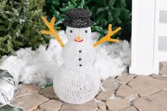 Snowman in the foreground. house entrance decorated for holidays. Christmas decoration. garland of fir tree branches and Stock Image