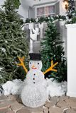 Snowman in the foreground. house entrance decorated for holidays. Christmas decoration. garland of fir tree branches and Royalty Free Stock Images