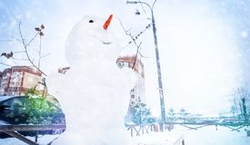 Snowman in a frosty winter, snowfall outside in the courtyard of residential panel houses. Snowman in a frosty winter, snowfall outside in the courtyard of royalty free stock photos
