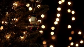 Snowman garland decoration on Christmas tree with bokeh lights in Christmas time.  stock video