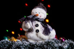 Snowman with a garland and tinsel. Snowman on the background of colored lights and garlands of Christmas tree decorations Stock Image