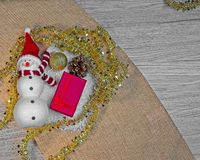 Snowman with gift box, burlap texture and wood background royalty free stock photography