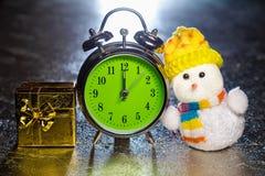 Snowman with gift box and retro alarm clock Stock Photos