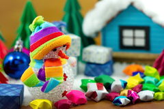 Snowman and gift box and small star paper on the snow field. Royalty Free Stock Images