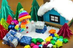 Snowman and gift box and small star paper on the snow field. Royalty Free Stock Photo