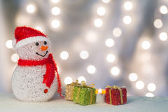 Snowman with gift boxes and candle. Happy snowman with red, green, and golden gift boxes and candle light Stock Photos