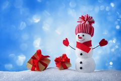 Snowman and gift boxes in winter snowy background. Christmas or New year greeting card