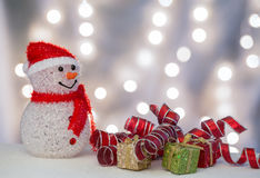 Snowman with gift packages and ribbons. Happy snowman with red, green, and golden gift boxes and red ribbon on the lights background Royalty Free Stock Photos