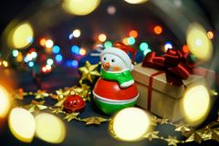 Snowman with gifts on the background of garlands and lights royalty free stock photo