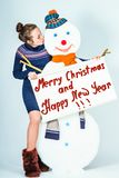 Snowman and girl kissing him. Holding in front of him poster, Happy New Year and Merry Christmas royalty free stock photography