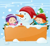 Snowman and girls behind wooden sign Royalty Free Stock Photos