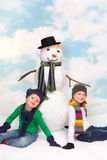 Snowman and girls Stock Photos