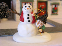 Snowman & Gnome. Miniature snowman figurine with a gnome peeking from behind Royalty Free Stock Photography