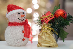 Snowman and golden bag. Snowman with red gift box, golden bag, red ball and lights on the background Stock Photography