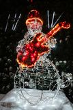 Snowman guitar player from luminous garlands with red guitar and top hat royalty free stock photography