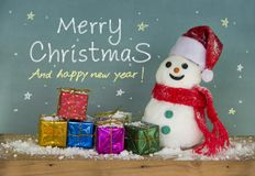 Snowman hat santa and Colorful gift box. Xmas Happy new year. Snowman hat santa and scarf red with a gift box on snow wooden floorand and scene green board Royalty Free Stock Images