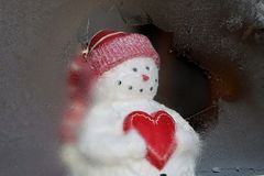 Snowman holding heart looking out window. Snowman holding heart looking out a frosty icy window in winter. Cute stock photos