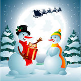 Snowman holding a present from Santa Claus. Two snowmen on the background of night sky with a bright moon and the silhouette of Santa Claus flying on a sleigh Stock Image