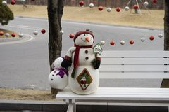 A snowman holding a welcome sign on a white bench on the side of the road stock photos