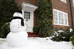 Snowman and house. Snowman at the front door of a house in winter Royalty Free Stock Photography