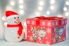 Snowman with huge gift box. Snowman with huge gift box with ligth background Stock Photos