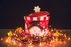 Snowman jar with lighted garland on black background.  Royalty Free Stock Photos