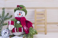 Snowman and a ladder ornamented with a fir branch. And a disco ball on a wooden surface Stock Images