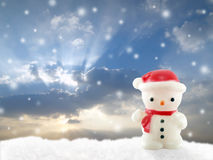 close up white snowman lamp on snow hill with falling snow on dramatic sky sunset background Royalty Free Stock Photography
