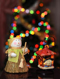 Snowman and lantern. Snowman with broom and lantern on a background of colored lights Stock Image