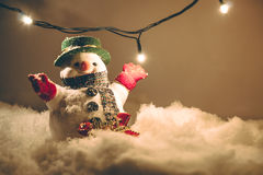 Snowman and light bulb stand among pile of snow at silent night, light up the hopefulness and happiness in Merry christmas and hap Royalty Free Stock Photo