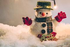 Snowman and light bulb stand among pile of snow at silent night, light up the hopefulness and happiness in Merry christmas and hap Stock Photography