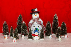 Snowman with little snowman and trees Royalty Free Stock Photography