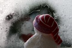 Snowman looking out window at night. Snowman looking out a frosty icy window in winter at night seeing reflection. Cute royalty free stock photography