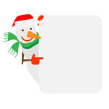 Snowman looks out of behind the wall Stock Photo