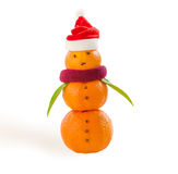 Snowman made of mandarins with little Santa hat on white. Stock Images