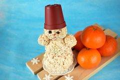 Snowman made of puffed rice. On blue background. Mandarins next to it Royalty Free Stock Photos
