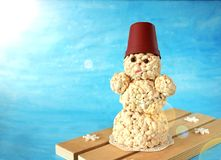 Snowman made of puffed rice. On blue background Royalty Free Stock Photos