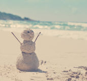 Snowman made of sand on a background of the tropical warm sea Stock Images