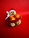 Snowman with mandarines. On red background Stock Photography