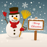 Snowman with Merry Christmas Sign. A funny snowman holding a broom and greeting in a snowy scene background with a Merry Christmas wooden sign. Eps file Royalty Free Stock Image